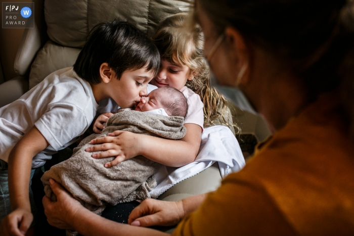Minas Gerais at home birth photography showing the First kiss between siblings right after birth