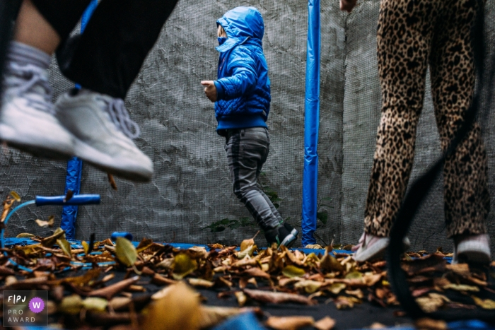 Day in the Life Eindhoven documentary family photography session showing some Trampoline fun with fall leaves