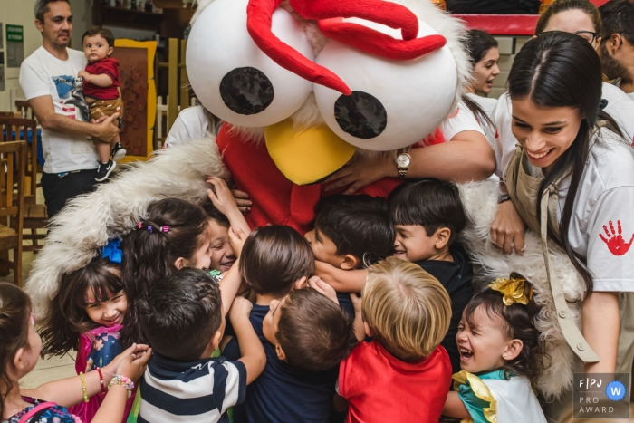 Campo Grande Day in the Life Session of documentary family photography Raised in a group hug with the rooster mascot of the party house
