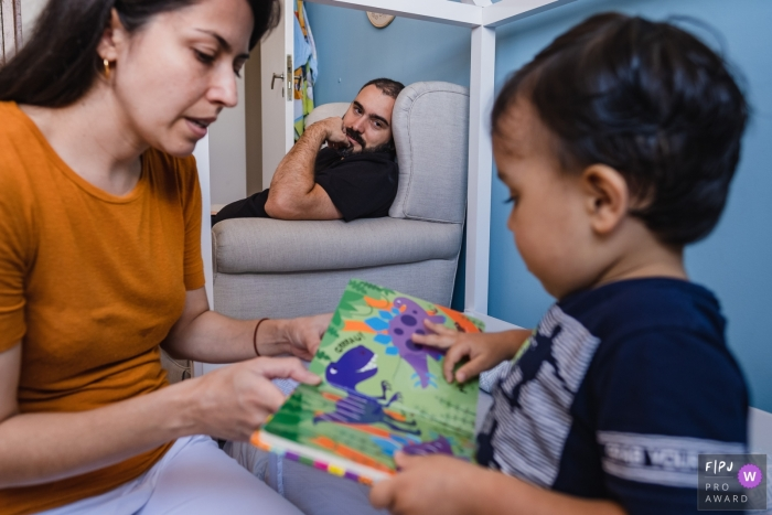 Sao Paulo at home Day in the Life photography showing dad watching his son reading with mommy