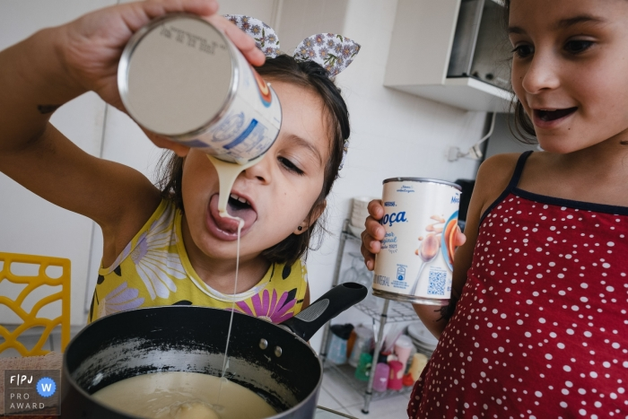 Sao Paulo Day in the Life documentary family photo showing a younger sister licking the sugar while preparing a recipe
