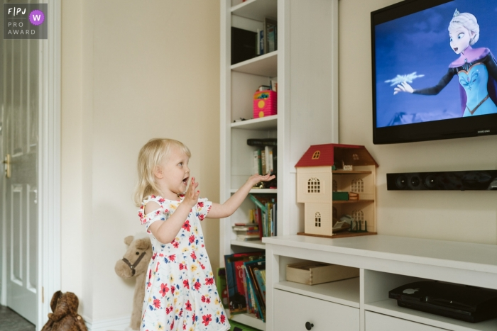 Surrey at home Day in the Life photography of a girl singing along to film on TV