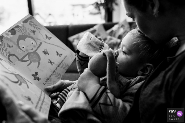 Day in the Life Flanders documentary family photography session of a baby with a bottle reading a book with mom