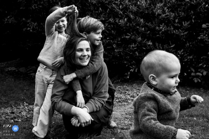 Flanders Day in the Life documentary family photo in BW of mom playing with the kids outside in the yard
