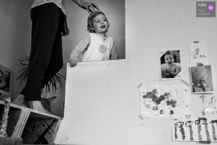 Flanders at home Day in the Life photography in BW showing a child climbing the stairs with a parent
