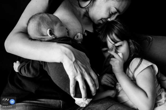 Florianopolis, Santa Catarina at home Day in the Life photography of a mother breastfeeding her newborn baby, on the sofa at home, with her eldest daughter receiving affection together