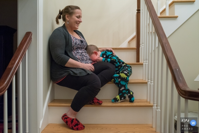 Day in the Life Connecticut documentary family photography session of a young boy having a meltdown as mom consoles him as they sit on the stairs