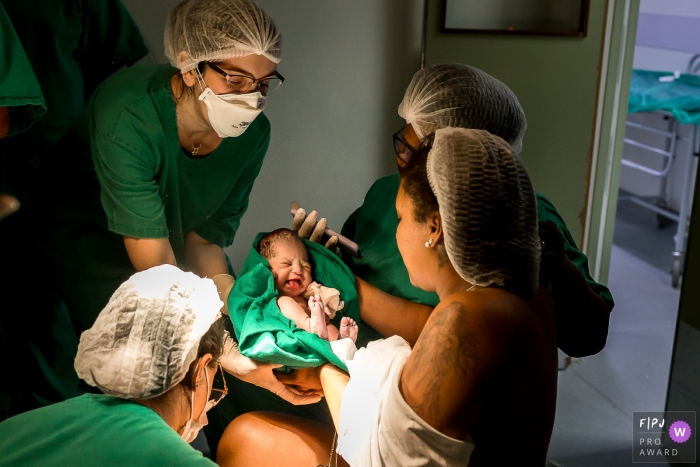 Moment-driven Hospital Unimed Campos birth photography of a mother handing baby over the a pediatrician