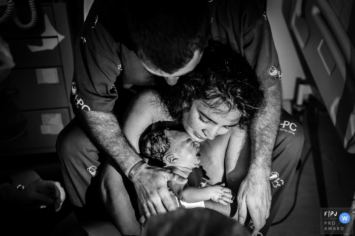 Moment-driven Hospital Plantadores de Cana birth photography covered in black and white of a mother and father holding their newborn child