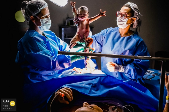 Moment driven São Luiz Anália Franco birth photojournalism image of a newborn being held up right after being born by cesarrean