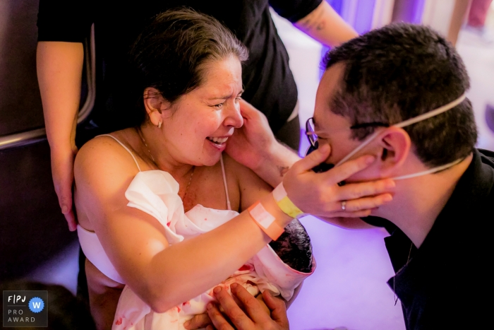 Moment driven Drenthe family photojournalism image of a mother elated with joy, looking into her husband's eyes with their newborn in her arms