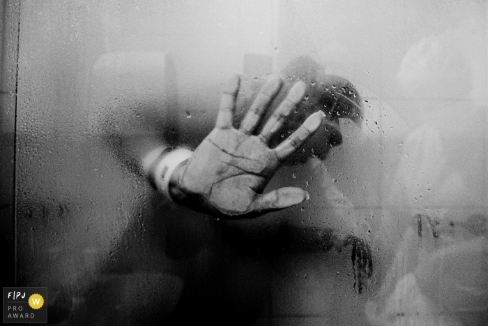 Moment driven Hopsital Santa Cruz birth photojournalism image of a hand on a steamy glass door of a shower during labor