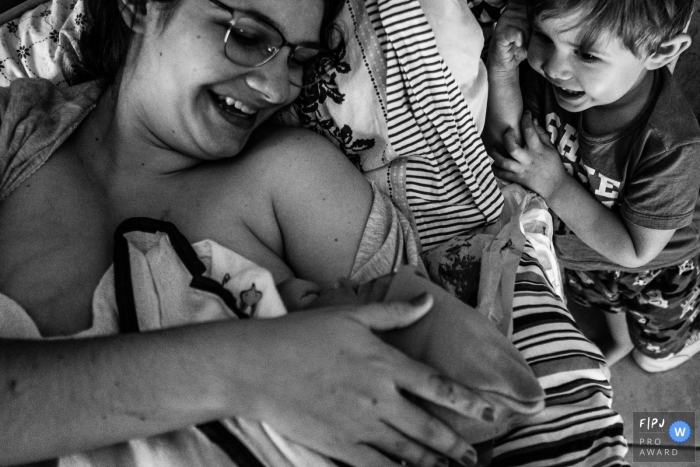 Moment-driven SP, Brazil birth photography showing The older brother's curiosity and emotion when meeting his younger brother