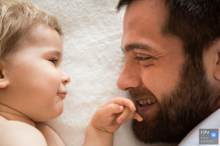 Moment driven Landes family photojournalism image of father and son laying down face to face