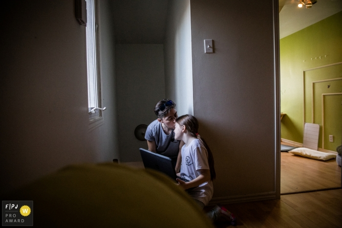 """Montreal family photo image.  Part of the series I did on Single Mothers homes during the Covid-19 Pandemic. This image shows a mother and her daughter right after her online ballet class seeking physical contact during times of """"virtual everything'"""
