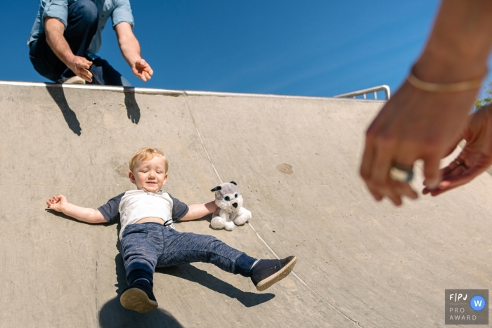 Moment-driven Kingston family photography of a Mother and father playing at the skatepark with their toddler