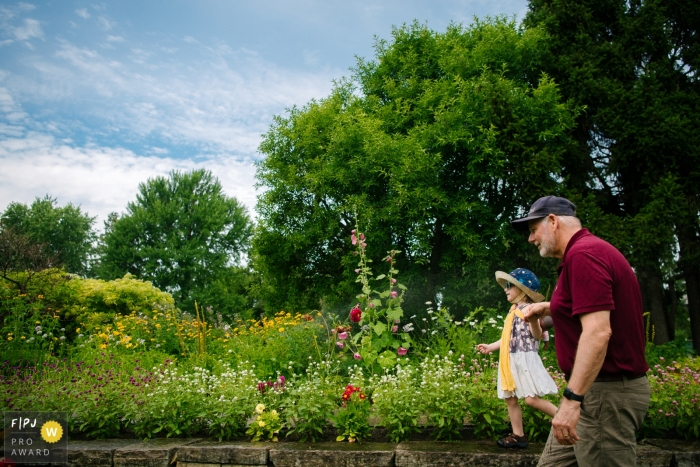 Moment driven Ottawa family photojournalism image of a young girl exploring the flower gardens with her grandfather