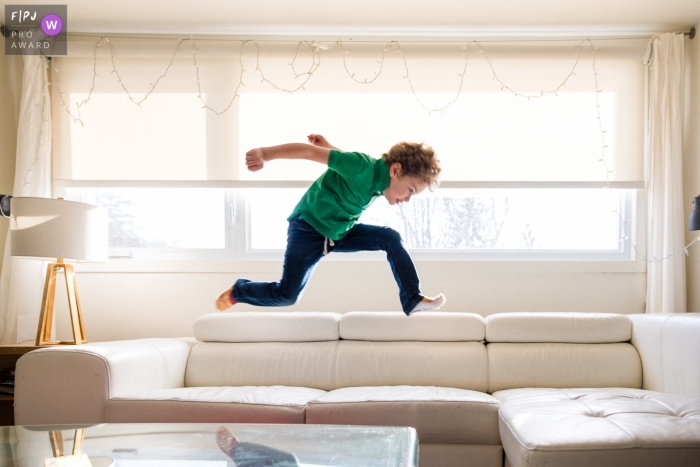 Moment driven Ontariio, Canada family photojournalism image of a boy jumping on the couch, breaking some rules