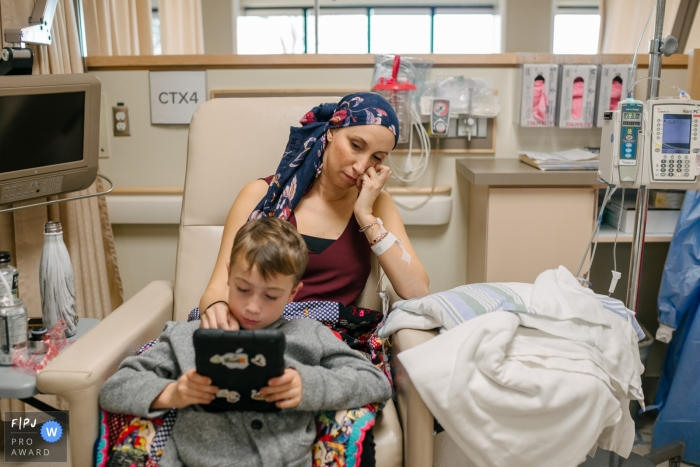 Moment driven Kingston family photojournalism image of a boy sitting with his mother during a chemotherapy treatment