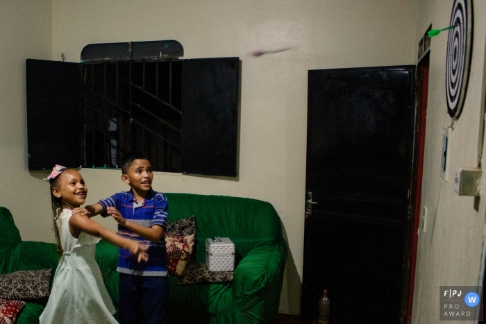 Moment-driven Roraima family photography of siblings playing darts