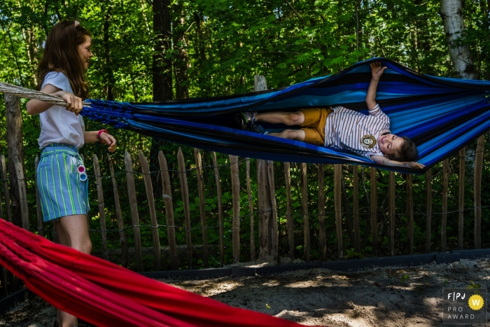 Moment driven Limburg family photojournalism image showing brother and sister fun on hammocks