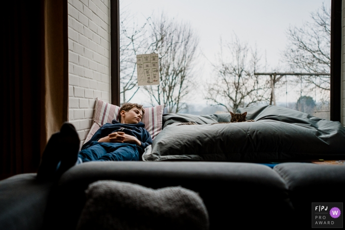 Moment driven Wallonie family photojournalism image capturing a napping teenager on the couch