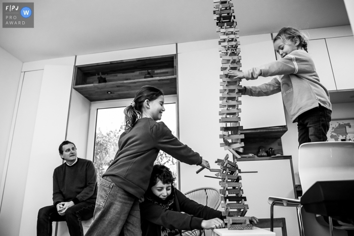 Moment driven Wallonie family photojournalism image of a kapla tower being knocked down