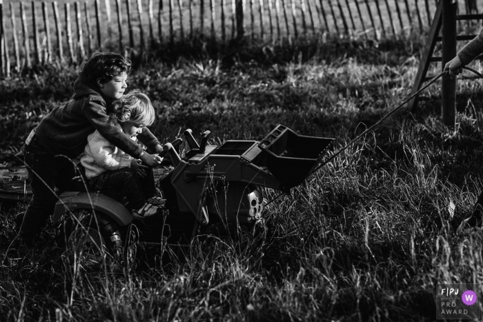 Moment-driven Wallonie family photography of a couple of kids riding a tractor