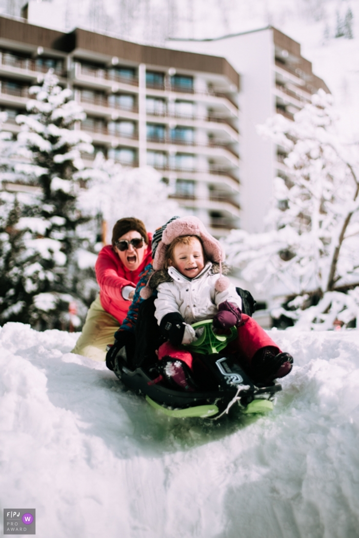 Moment-driven Savoie family photography of a mother with her two children sledding on the snow