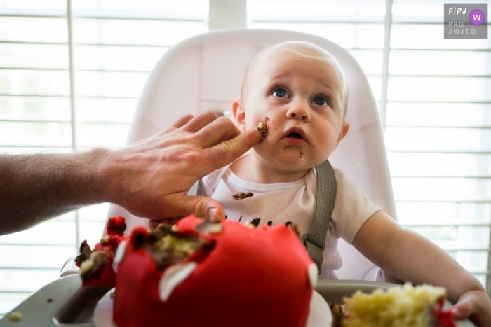 Moment-driven Atlanta family photography of a finger reaching in with cake frosting to the babies cheek