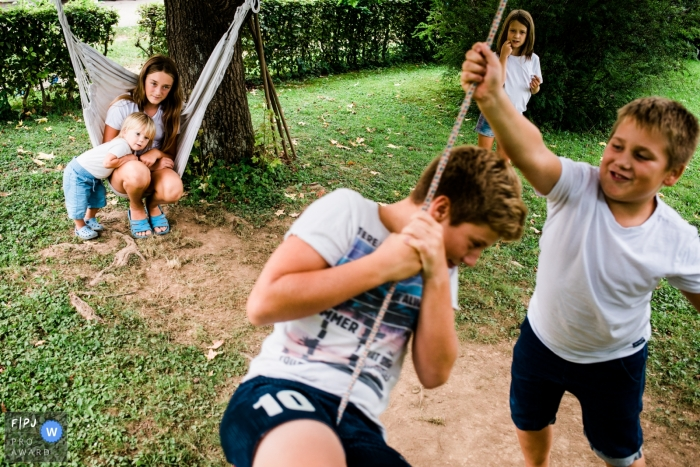 Moment-driven Ljubljana family photography of kids having fun on hammocks and swings