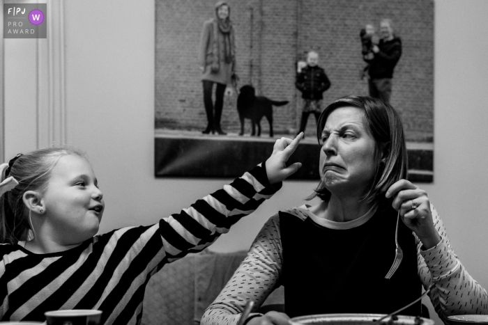 Moment driven Zwolle family photojournalism image of a Funny moment between mom and daughter, check out the 'perfect'picture in the background