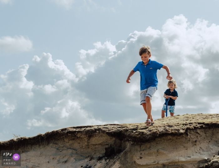 Moment driven Amsterdam family photojournalism image of two brothers at the dunes, one is about to jump off an edge