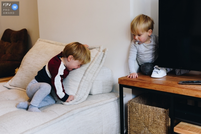 Moment driven Amsterdam family photojournalism image Twin brothers around the TV-screen, one of them is enjoying himself, the other not so much