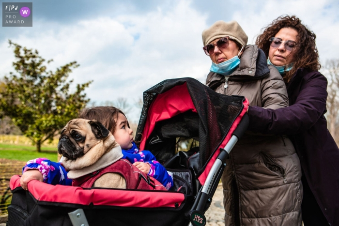 Moment driven Istanbul family photojournalism image of a mother and grandmother pushing a young girl with dog in a stroller