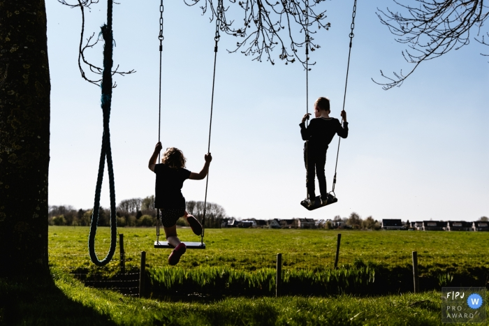 Moment driven Groningen family photojournalism image of a brother and sister standing on the seats of swings and they soar