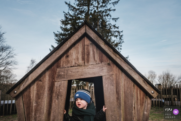 Moment driven Belgium family photojournalism image of a little boy playing in a tiny house