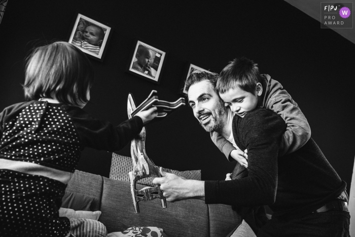 Moment driven Antwerpen family photojournalism image of a dad involved in a sword fight with his children