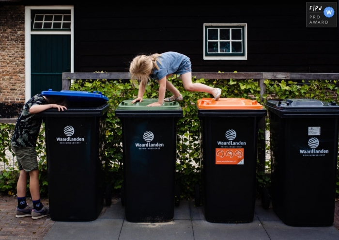 Moment driven Netherlands family photojournalism image of kids hoping over trash cans