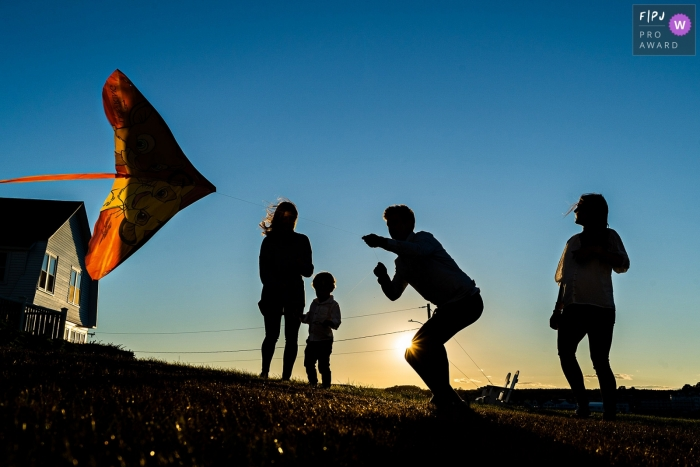 Moment driven New Hampshire family photojournalism image of a family flying a Lion King kite at sunset in Maine