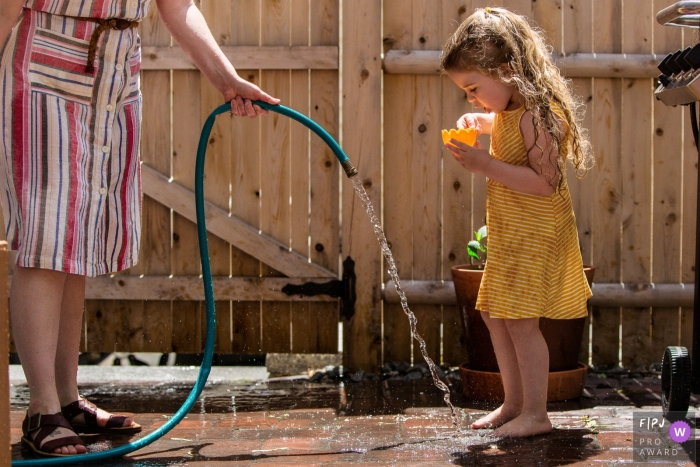 Moment driven New Hampshire family photojournalism image of Mom holds hose for young daughter to fill her cup on a hot day