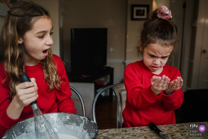 Moment-driven New Hampshire family photography of sisters making pancakes react to messy batter on little sister's hands