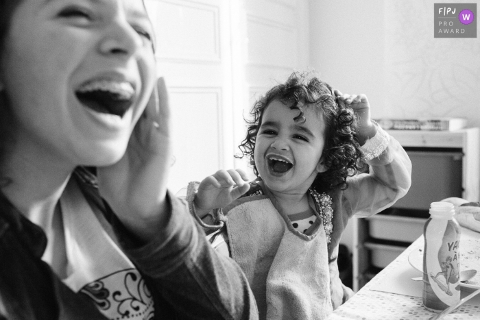 Moment driven Paris family photojournalism image of a laughing session at the meal table