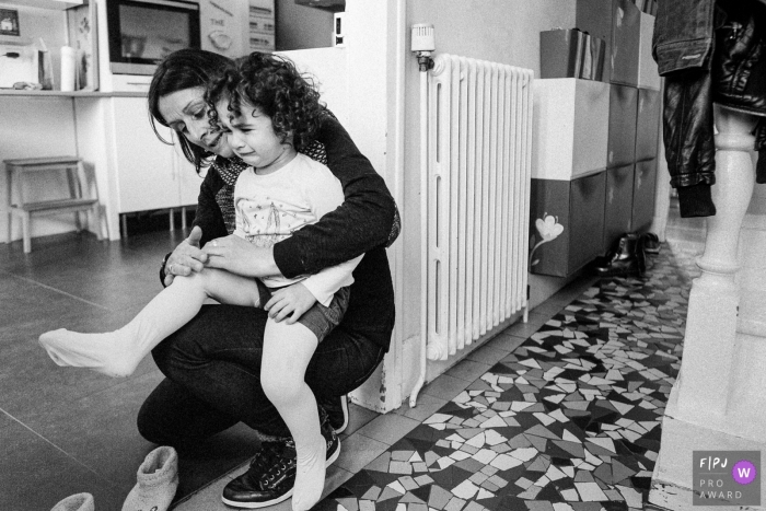 Moment-driven Ile-de-France family photography of a little girl crying on her mom's knees