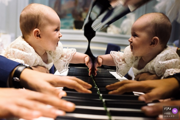 Moment driven Paris family photojournalism image of a baby looking at their reflection on a piano