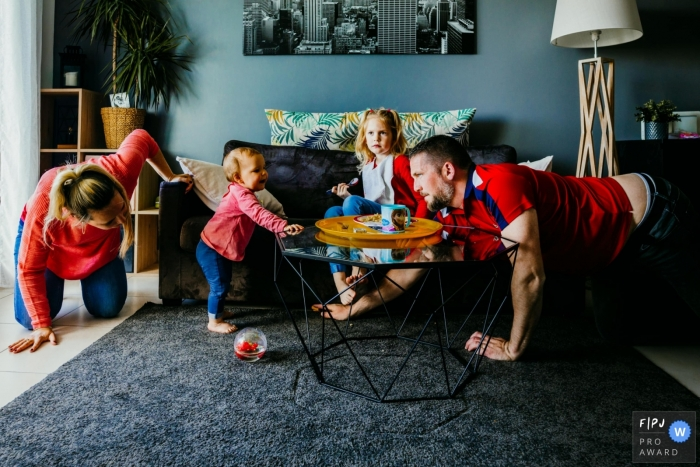 Moment driven Var family photojournalism image capturing the seeking of an object that has disappeared in the livingroom