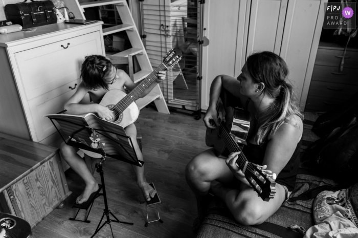 Moment-driven Gard family photography of a mom teaching her son how to play the guitar