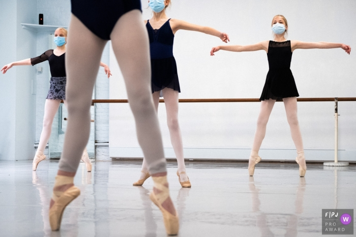 Moment driven Flanders family photojournalism image of girls in a ballet class