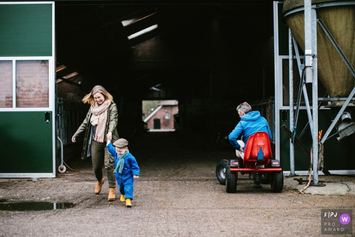 Moment-driven Netherlands family photography of a mother and child exiting a barn on their vaction on the farm