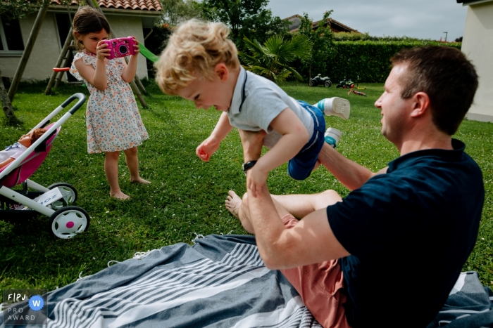 Moment-driven Occitanie family photography of dad and his children playing outside in the yard